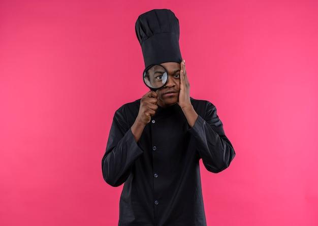 シェフの制服を着た若い気になるアフリカ系アメリカ人の料理人は、コピースペースでピンクの背景に分離された虫眼鏡またはルーペを通して見えます