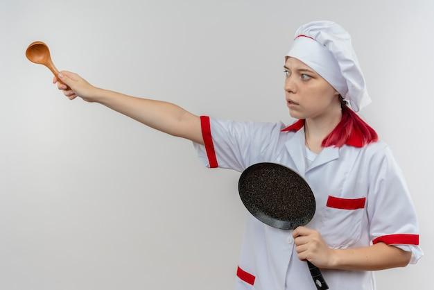 シェフの制服を着た若い気になる金髪の女性シェフは、フライパンを保持し、白い壁に分離されたスプーンで横を指しています