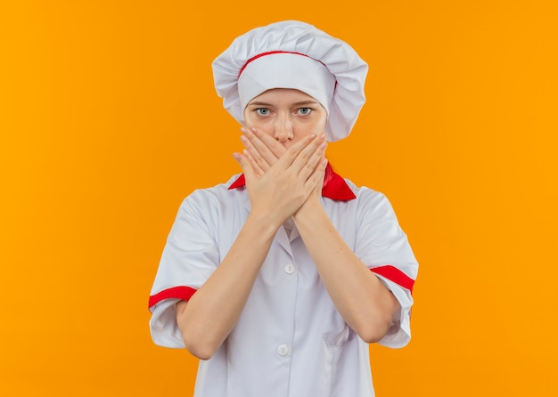 シェフの制服を着た若い気になる金髪の女性シェフは、オレンジ色の壁に隔離された手で口を保持します。