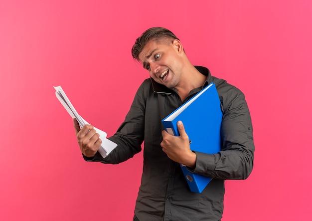 Giovane uomo bello biondo ansioso tiene fogli di carta e cartelle di file parlando al telefono isolato su spazio rosa con spazio di copia