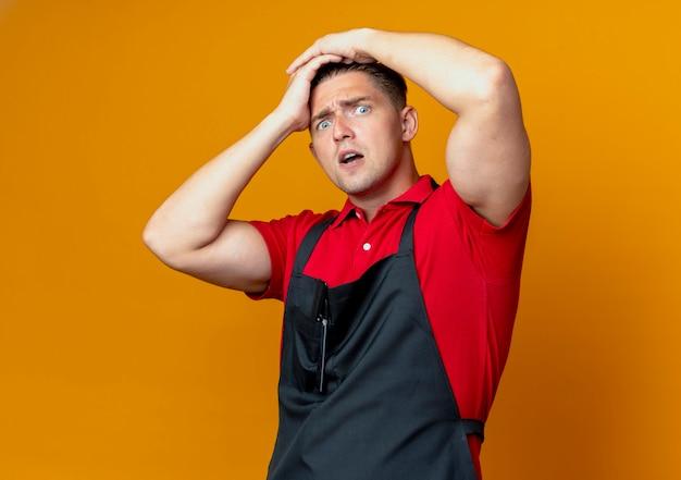 Молодой взволнованный светловолосый парикмахер в униформе держит голову изолированной на оранжевом пространстве с копией пространства