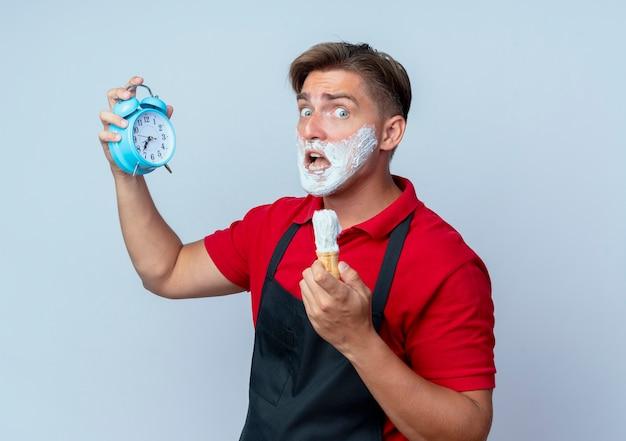 Молодой взволнованный светловолосый парикмахер в униформе измазал лицо пеной для бритья, держа будильник и щетку для бритья, изолированную на белом пространстве с копией пространства