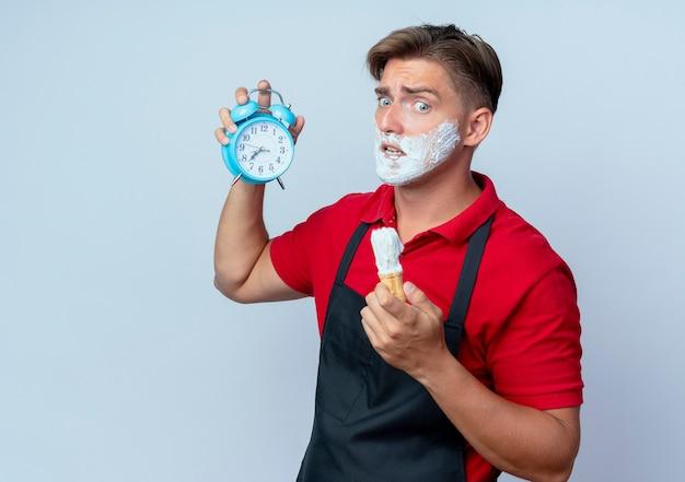 Молодой взволнованный светловолосый парикмахер в униформе, измазанный пеной для бритья, держит будильник и щетку для бритья, глядя вниз на белом пространстве с копией пространства