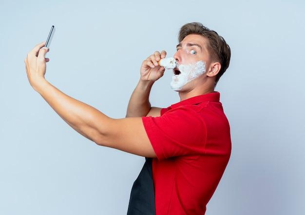 制服を着た若い気になる金髪の男性理髪師は、コピースペースと白いスペースで隔離の電話を保持しているシェービングフォームで顔を横に塗って立っています