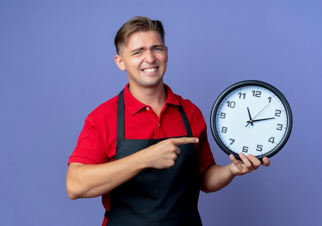 Il giovane barbiere maschio biondo ansioso in uniforme tiene e indica l'orologio isolato sullo spazio viola con lo spazio della copia