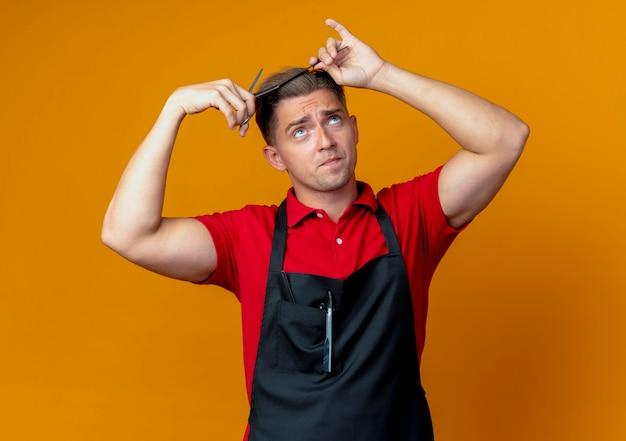 Barbiere maschio biondo ansioso giovane in uniforme cercando di tagliare i capelli con il pettine e le forbici cercando isolato su spazio arancione con spazio di copia