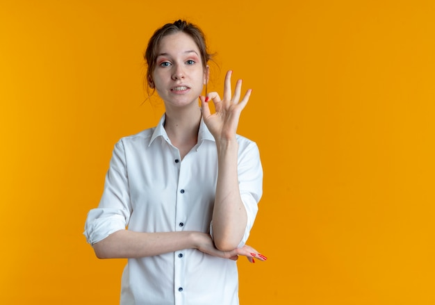 Young anxious blonde russian girl gestures ok hand sign