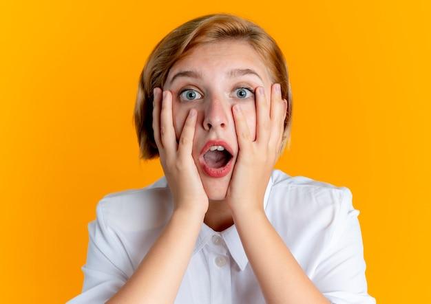 La giovane ragazza russa bionda ansiosa tiene il fronte che guarda l'obbiettivo isolato su priorità bassa arancione con lo spazio della copia
