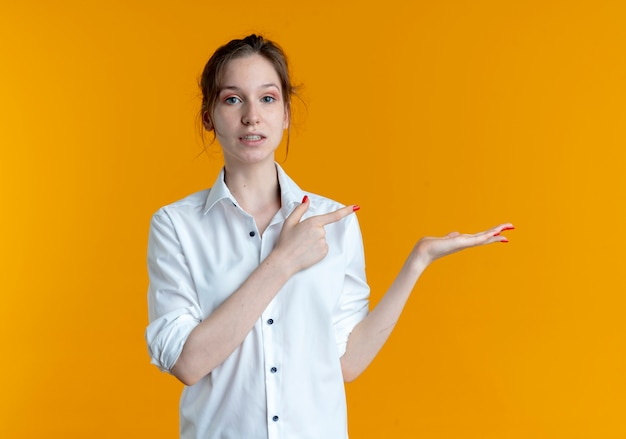 Young anxious blonde russian girl points at empty hand isolated on orange background with copy space