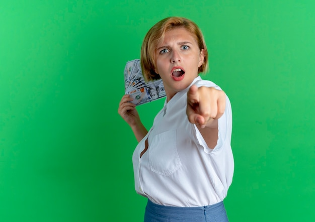 Young anxious blonde russian girl stands sideways holds money and points at camera isolated on green background with copy space