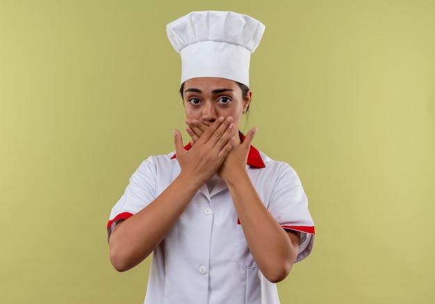 La giovane ragazza caucasica ansiosa del cuoco in uniforme dello chef chiude la bocca con le mani isolate su fondo verde con lo spazio della copia
