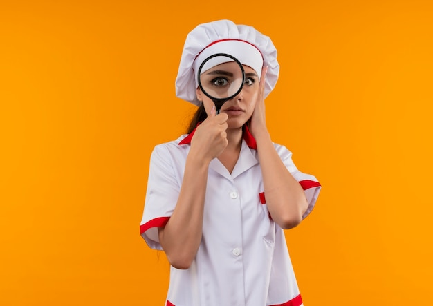 La giovane ragazza caucasica ansiosa del cuoco in uniforme del cuoco unico osserva tramite la lente d'ingrandimento o la lente di ingrandimento isolata su priorità bassa arancione con lo spazio della copia