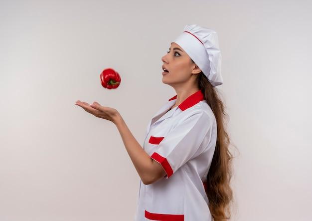 La giovane ragazza caucasica ansiosa del cuoco in uniforme del cuoco unico finge di catturare il peperone rosso isolato su fondo bianco con lo spazio della copia