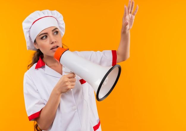 シェフの制服を着た若い気になる白人料理人の女の子は、大きなスピーカーを保持し、コピースペースでオレンジ色の背景に分離された手を上げます