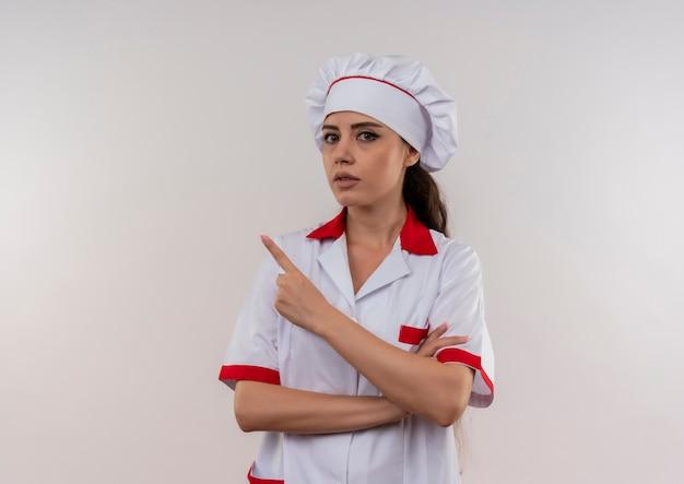 シェフの制服を着た若い気になる白人料理人の女の子は、コピースペースで白い背景で隔離の側を指しています