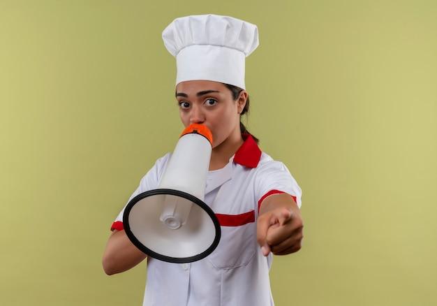 シェフの制服を着た若い気になる白人料理人の女の子がスピーカーから叫び、コピースペースで緑の背景に隔離された前方を指しています