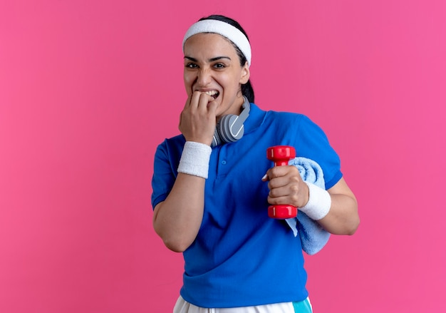 ヘッドバンドとリストバンドを身に着けている若い気になる白人スポーティな女性は、コピースペースでピンクの背景に分離されたダンベルとタオルを保持している指を噛みます
