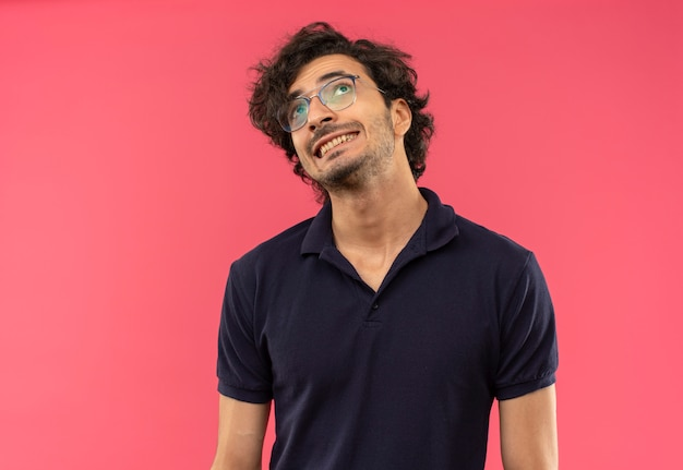 光学ガラスの黒いシャツを着た若い不安な男は歯を食いしばってピンクの壁に孤立して見上げる