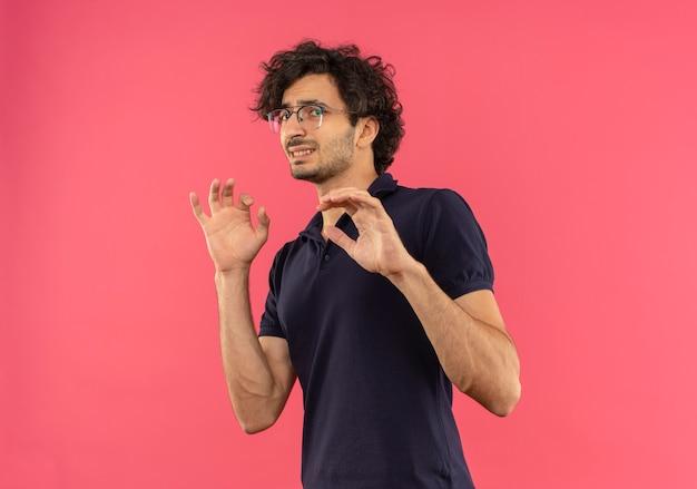 光学ガラスの黒いシャツを着た若い不安な男は手を上げて、ピンクの壁に孤立して防御するふりをします