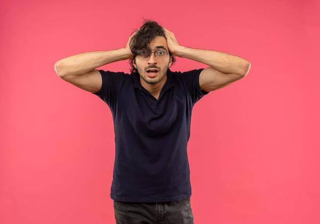 光学メガネと黒のシャツを着た若い不安な男は頭を保持し、ピンクの壁に孤立して見える