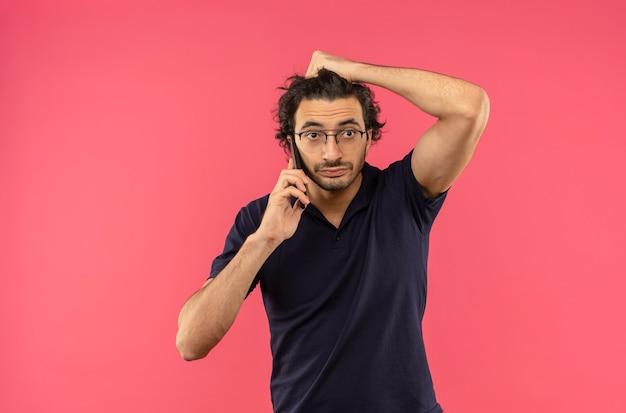 光学メガネをかけた黒いシャツを着た若い不安な男が電話で話し、ピンクの壁に隔離された頭を保持します。