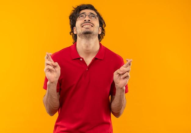 Молодой взволнованный мужчина в красной рубашке с оптическими очками скрещивает пальцы и смотрит вверх изолированно на оранжевой стене