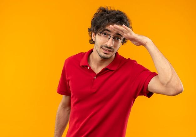 光学ガラスの赤いシャツを着た若い不安な男は、オレンジ色の壁に遠く離れた何かを見ようと額に手のひらを保ちます