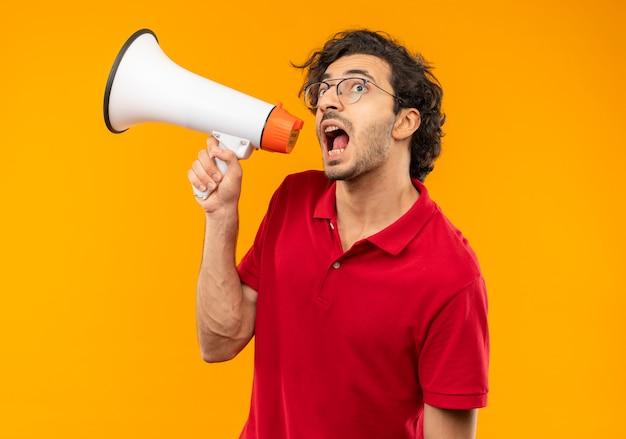 光学メガネと赤いシャツを着た若い不安な男は、オレンジ色の壁に分離されたスピーカーを通して叫ぶ