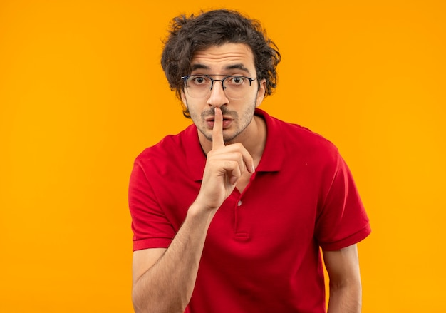Il giovane uomo ansioso in camicia rossa con i gesti dei vetri ottici mantiene il segno di silenzio isolato sulla parete arancione