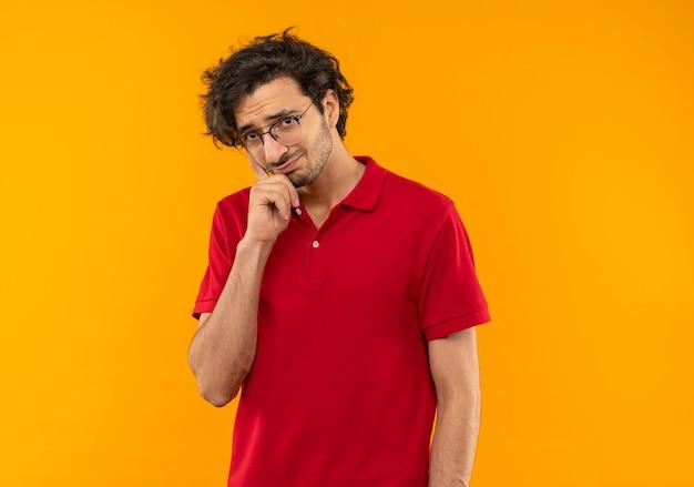 Giovane uomo ansioso in camicia rossa con occhiali ottici mette la mano sul mento e sembra isolato sulla parete arancione