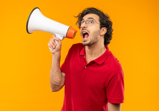Young anxious man in red shirt with optical glasses shouts through loud speaker isolated on orange wall