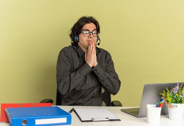 L'uomo giovane lavoratore di ufficio di anxius sulle cuffie in vetri ottici si siede alla scrivania con strumenti di ufficio utilizzando e guardando il computer portatile tenendo le mani insieme