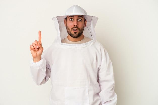 いくつかの素晴らしいアイデア、創造性の概念を持つ白い背景に分離された若い養蜂白人男性。