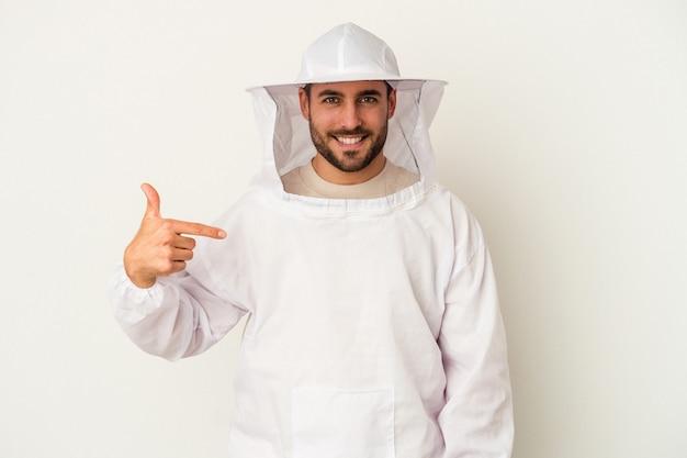 シャツのコピー スペースを手で指している白い背景の人に分離された若い養蜂白人男性、誇りと自信を持って