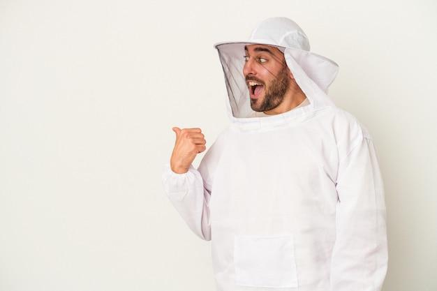養蜂の若い白人男性は、白い背景に親指を離し、笑いながら屈託のないポイントで孤立した。