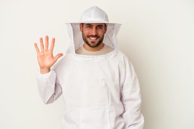 指で5番を示す陽気な笑顔の白い背景で隔離の若い養蜂白人男性。
