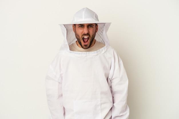 Молодой человек кавказского пчеловодства, изолированные на белой стене, кричал очень сердито и агрессивно.