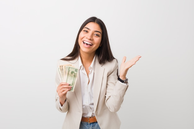 Young arab business woman holding dollars celebrating a victory or success