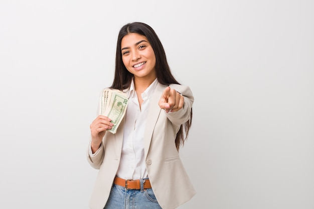 Young arab business woman holding dollars cheerful smiles pointing to front.
