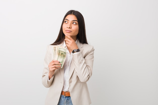 Young arab business woman holding dollars looking sideways with doubtful and skeptical expression.