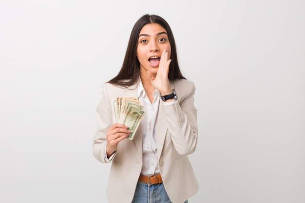 Young arab business woman holding dollars shouting excited to front.