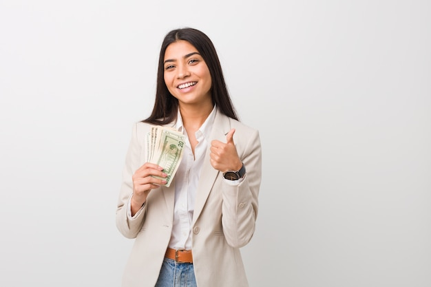 Young arab business woman holding dollars smiling and raising thumb up