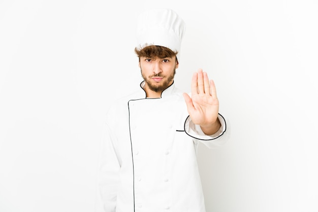 Young arab cook man standing with outstretched hand showing stop sign, preventing you.