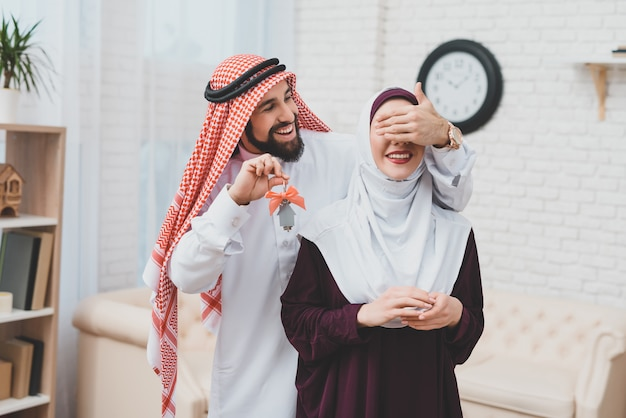 Young arab couple moving man closes eyes for wife