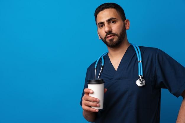 Молодой арабский врач пьет чашку кофе, стоя на синем фоне