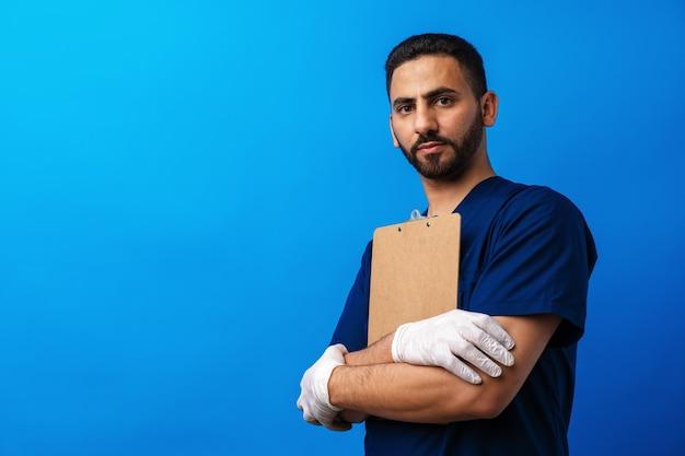 Молодой арабский врач держит буфер обмена на синем фоне