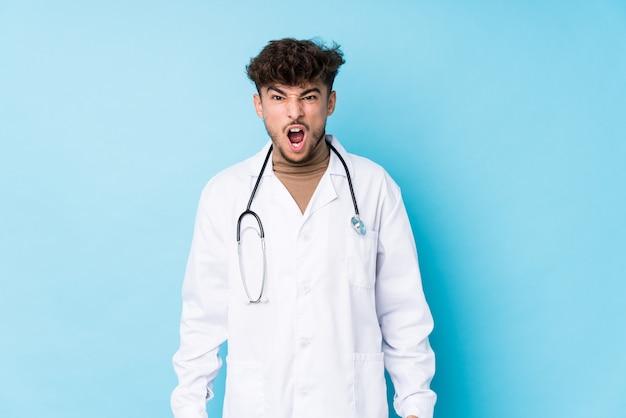 젊은 아랍 의사 남자는 매우 분노하고 공격적인 비명을 우상화했습니다.