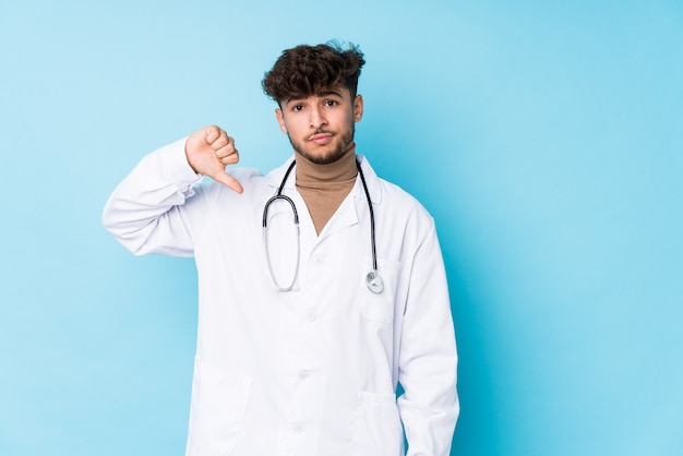 Young arab doctor man idolated showing a dislike gesture, thumbs down. disagreement concept.