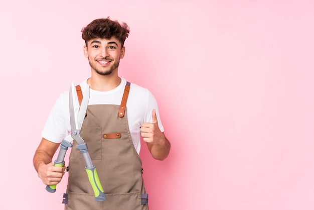 Молодой арабский садовник изолирован, улыбаясь и поднимая палец вверх