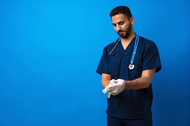 Молодой арабский мужчина-врач, стоящий на синем фоне